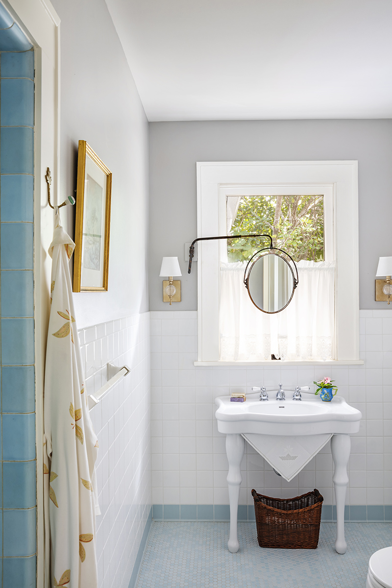Restored Guest Powder Bathroom With Original Blue Shower Tiles, New Mosaic Penny Floor Tile, Antique Mirror, And Vintage Inspired Sink.