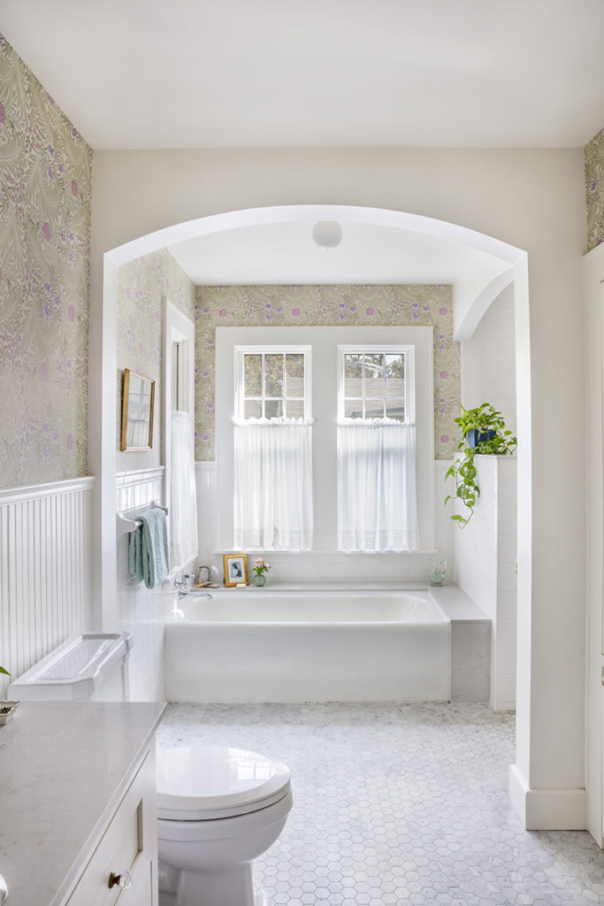 New master bathroom with restored original tub, new arched opening to shower, and marble tile floors